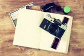 Top view of old vintage camera and pictures over wooden brown background. — Stockfoto
