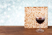 Passover background. wine and matzoh (jewish passover bread) over wooden background. glitter background. — Stock Photo