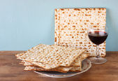 Passover background. wine and matzoh (jewish passover bread) over wooden background. — Foto de Stock