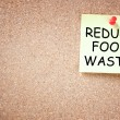 Sticky note pinned to corkboard with phrase reduce food waste — Stock Photo #41845081
