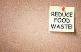Sticky note pinned to corkboard with the phrase reduce food waste — Stock Photo