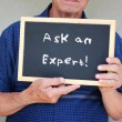 Close up of senior man holding blackboard with the phrase ask an expert written on to — Stock Photo #48221881