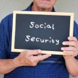 Senior man holding blackboard with the phrase social security written on it. — Stock Photo #48221903