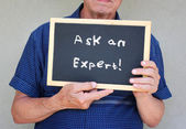 Close up of senior man holding blackboard with the phrase ask an expert written on to — Stock Photo