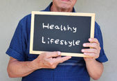 Close up of senior man holding a blackboard with the phrase good health equals good life — Stock Photo