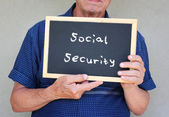 Senior man holding blackboard with the phrase social security written on it. — Stock Photo