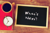 Clock, coffee, and blackboad with the phrase whats next? written on it. — Foto Stock