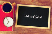 Blackboard with the word deadline written on it, clock and coffee cup over wooden board — Stock Photo