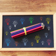 Top view of blackboard and pencils stack and various light bulbs drawing in color — Stock Photo #50557869
