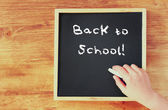 Kid hand holding chalk over blackboard with the phrase back to school written on it. — Stock Photo