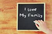 Kid hand holding chalk over blackboard writing i love my family. — Stock Photo