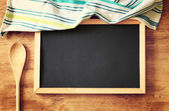 Top view of blackboard and wooden spoon over wooden table. filtered image — Stock Photo