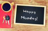 Blackboard with the phrase happy monday written on it, coffee cup and car keys. filtered image. — Stock Photo