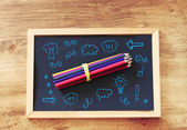 Top view of pencils stack over blackboard and various drawing — Stock Photo