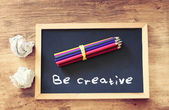 Top view of crumpled paper and pencils stack over blackboard with the phrase be creative. — ストック写真