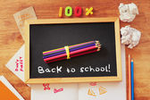 Top view of blackboard with the phrase back to school, stack of pencils and crumpled paper. — Stock Photo