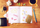 Top view of messy table with notebook with doodles, coffee cup, papers and keys. — Stock Photo