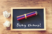 "Top view of crumpled paper and pencils stack over blackboard with the phrase ""stay sharp"". — Stock Photo"