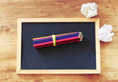Top view of blackboard , stack of pencils and crumpled paper. — Stock Photo