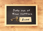 The phrase step out of your comfort zone written on blackboard — Stock Photo