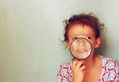 Kid looking through magnifying glass . — Foto Stock