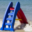 Children play at sea on holiday, red slide or slip — Stock Photo #13254253