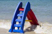 Children play at sea on holiday, red slide or slip — Stock Photo