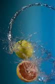 Fresh lemons and apples under water jet splash — Stock Photo