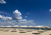 Panoramic view of straw umbrella on an empty beach — Stock Photo