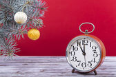 Christmas balls with an alarm clock and fir branches — Stock Photo