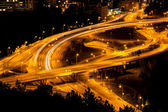 Abstract lights from cars on road junction with bridge — Stock Photo