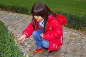 少女スクワットし、草を見て — ストック写真