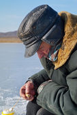 Old man on winter fishing — Stock Photo