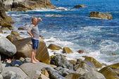 Man on stones at surf — Stock Photo