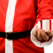 Santa Claus holding a gift - Stock Photo