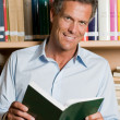 Mature man in library — Stockfoto