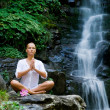 Young woman doing yoga near waterfall — Stok fotoğraf