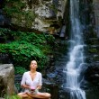 Young woman doing yoga with lotus flower — Stock Photo