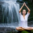 Woman doing yoga in the nature - Stock Photo