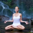 Young woman doing yoga in the water - Stock Photo