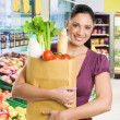 Young woman with grocery bag in market - Stock Photo