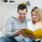 Young couple reading magazine — Stock Photo