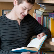 Happy student reading book in a library — Stock Photo #12658098