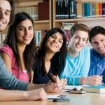 Grupo sonriente de estudiantes en una biblioteca — Foto de Stock