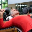Stock Photo: Exercising with dumbells at gym