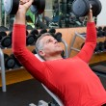 Mature man lifting weights — Stock Photo