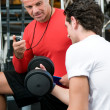 Young man with instructor at gym — Stock Photo