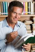 Mature man reading book — Stock Photo