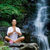 Young woman doing yoga near waterfall — Stock Photo