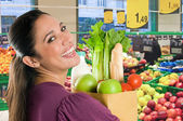 Young woman doing shopping in a supermarket — Stock Photo